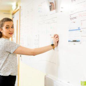Kobieta przykleja listę zadań do ściany magnetycznej
